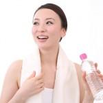 汗をかきスポーツドリンク飲む女性