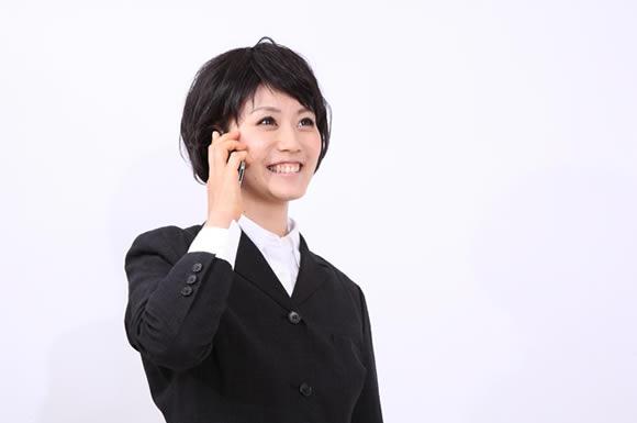 携帯を掛けるスーツの女性