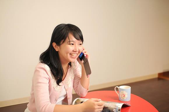 携帯をかけて勉強する女性